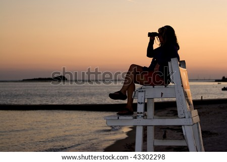 A silhouette of a woman looking with binoculars at the beach while sitting on a lifeguard chair. - stock photo