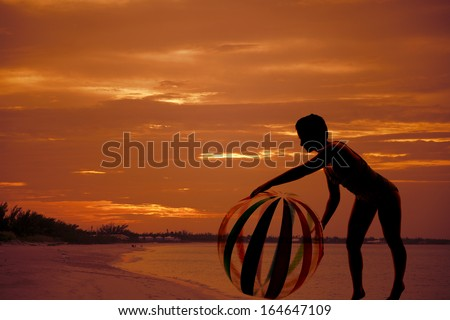 A silhouette of a woman on a beach playing with a beach ball. - stock photo