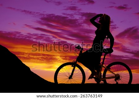 a silhouette of a woman on her bike, resting before heading up a hill. - stock photo