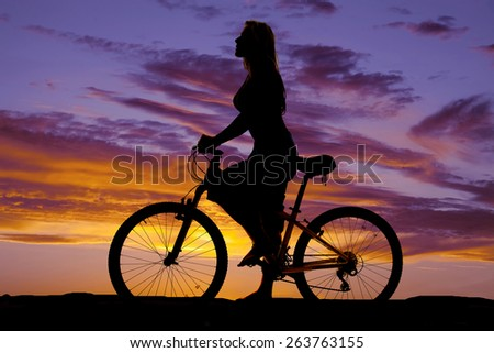 A silhouette of a woman on her bike, standing and looking forward. - stock photo