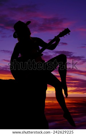 a silhouette of a woman playing her guitar in the outdoors. - stock photo