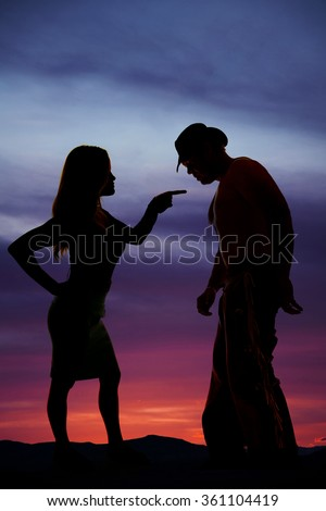a silhouette of a woman pointing her finger at the cowboy.