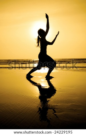 A silhouette of a woman practicing yoga at sunset on beach