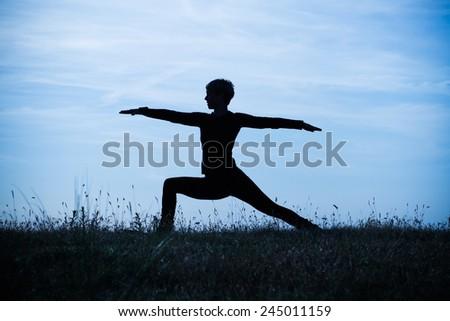 A silhouette of a woman practicing yoga,intentionally toned image.Yoga-Virabhadrasana /Warrior pose - stock photo