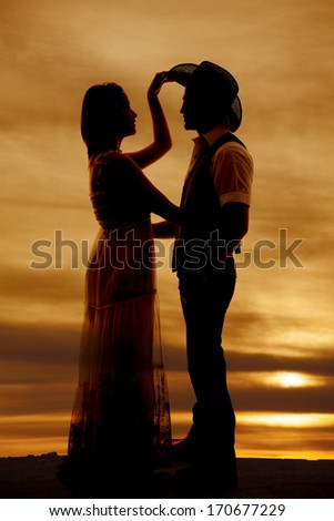 a silhouette of a woman reaching up to touch her cowboys hat. - stock photo