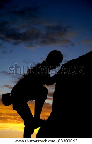 A silhouette of a woman rock climbing with a beautiful sunset in the back ground. - stock photo