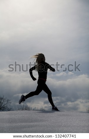 A silhouette of a woman running through the snow