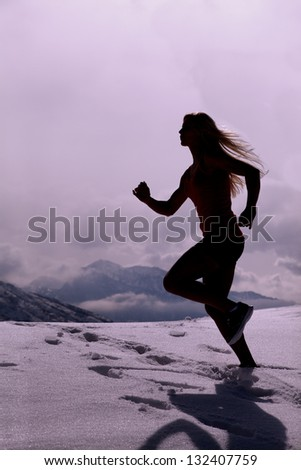 A silhouette of a woman running through the snow with mountains in the background.