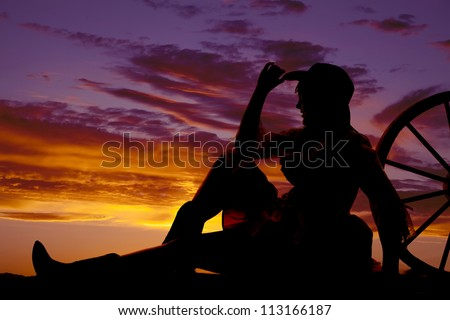 a silhouette of a woman sitting and leaning back against a wagon wheel with a beautiful sunset.