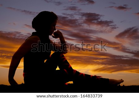 a silhouette of a woman sitting and thinking. - stock photo