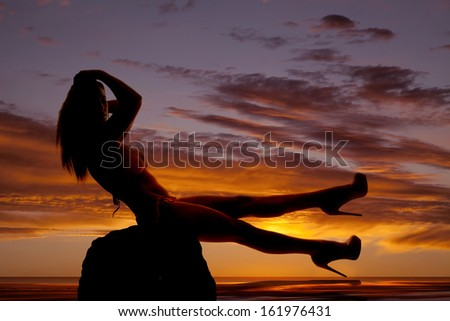A silhouette of a woman sitting in a bikini in the sunset.