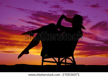 A silhouette of a woman sitting in a wicker chair with her hat on relaxing. - stock photo