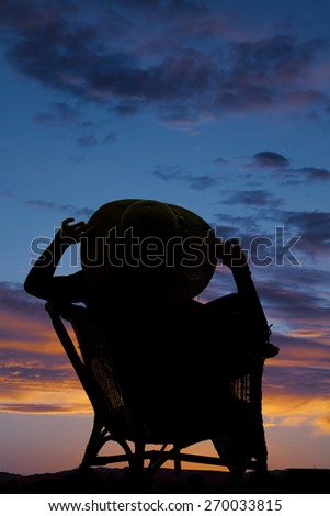 a silhouette of a woman sitting in her wicker chair enjoying the beautiful skies. - stock photo