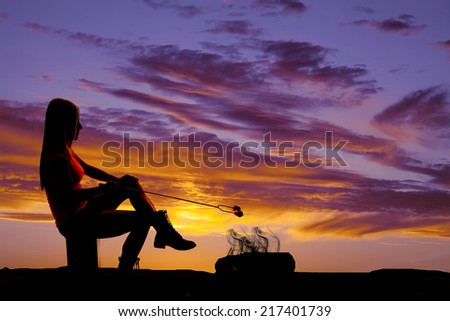 A silhouette of a woman sitting in the outdoors, with a fire roasting a marshmallow. - stock photo