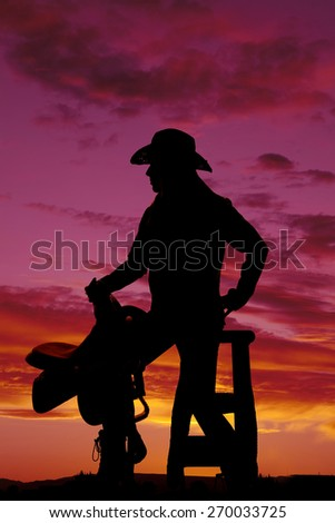 a silhouette of a woman sitting on a stool holding on to her saddle. - stock photo