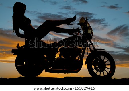 A silhouette of a woman sitting on her bike with her shoes on the tank of the bike - stock photo