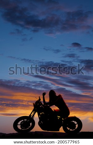 a silhouette of a woman sitting on her motorcycle  enjoying the night sky.