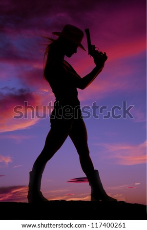 A silhouette of a woman standing and holding a weapon. - stock photo