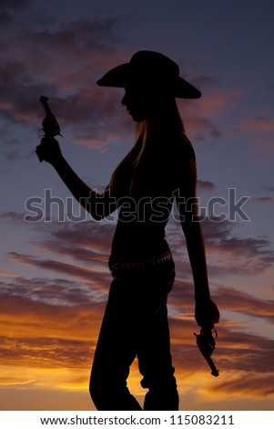 a silhouette of a woman standing holding two guns with a colorful sky behind her. - stock photo