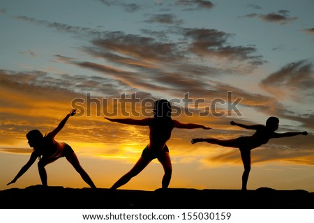A silhouette of a woman standing up doing poses and exercising in the outdoors. - stock photo