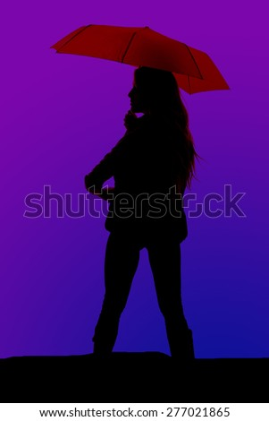 A silhouette of a woman standing with an umbrella in her hands. - stock photo