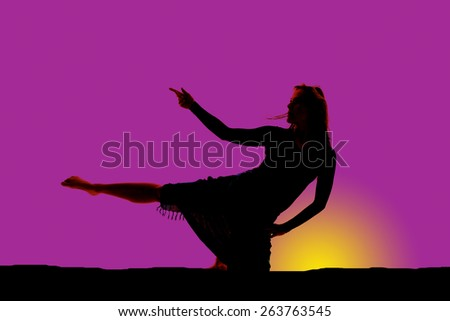 A silhouette of a woman stretching in a yoga pose in her sarong. - stock photo