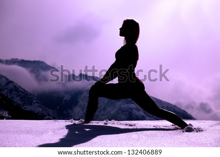 A silhouette of a woman stretching out her body in the snow in the outdoors.