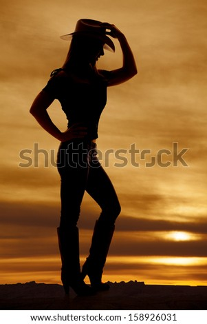 A silhouette of a woman touching her hat looking down. - stock photo