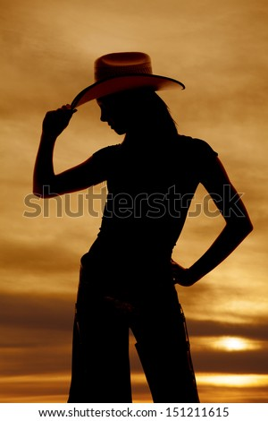 A silhouette of a woman touching the brim of her hat.