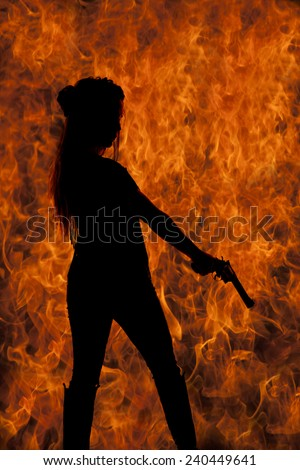 a silhouette of a woman with a fire back ground pointing her gun to the ground. - stock photo