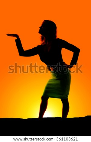 A silhouette of a woman with her hand out in her dress.