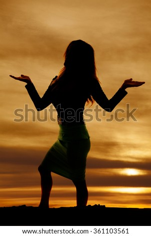 a silhouette of a woman with her hands up in the air.