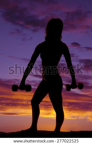 A silhouette of a woman working out with weights in the outdoors. - stock photo
