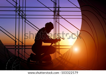 A silhouette of a worker-welder. - stock photo