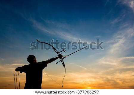 A silhouette of an archer drawing his bow and aiming upwards with colorful and dramatic sky as background - stock photo