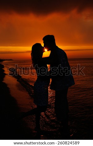 a silhouette of couple in love at sunset - stock photo