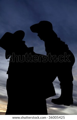 A silhouette of cowboy and child together.
