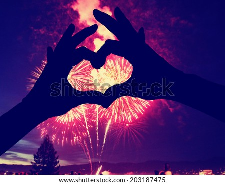 a silhouette of hands shaped in a heart against a 4th of july fireworks background - stock photo