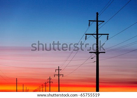 A silhouette of high voltage power lines against a dramatic and colorful sky at sunrise or sunset.