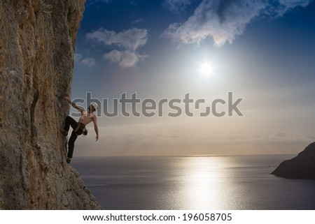 A silhouette of man climbing on rock, mountain at sunset. Adrenaline, strenght, ambition  - stock photo