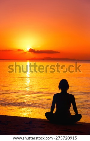 A silhouette of meditating woman at the sea shore at orange sunset background.
