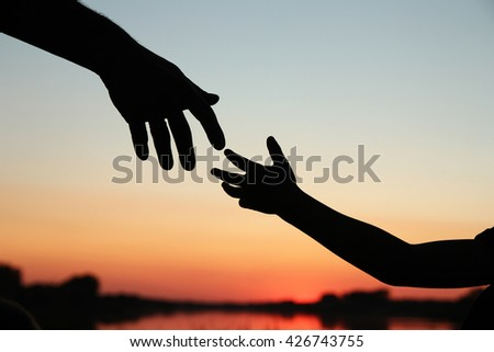 a silhouette of parent holds the hand of a small child - stock photo