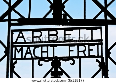 A silhouette of the infamous message on gates to concentration camps on a sky background. - stock photo