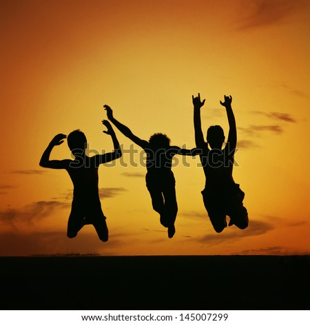 a silhouette of three kids jumping