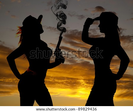 a silhouette of two women in their cowgirl hats one has a gun with smoke coming out of the pistol. - stock photo