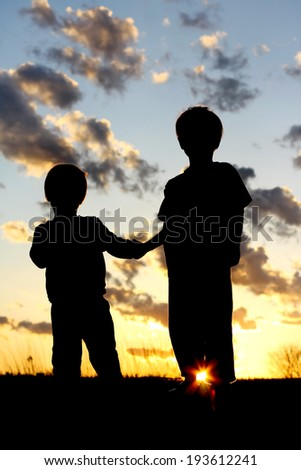 a silhouette of two young children; a little boy and his baby brother, lovingly holding hands in front of a beautiful sunset in the sky.
