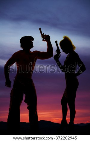A silhouette of woman with a pistol, standing next to her cowboy who is holding on to a gun. - stock photo