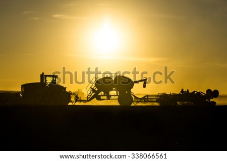 A silhouette photograph of a tractor and air drill planting and seeding wheat on an organic farm at the end of the day.