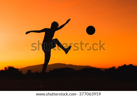 a silhouette picture of the boy is playing football in the sunshine day.