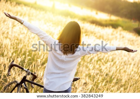 A silhouette woman in the early morning with her vintage bicycle. Image create for business, health, lifestyle of people relaxing in meadow with golden light. - stock photo